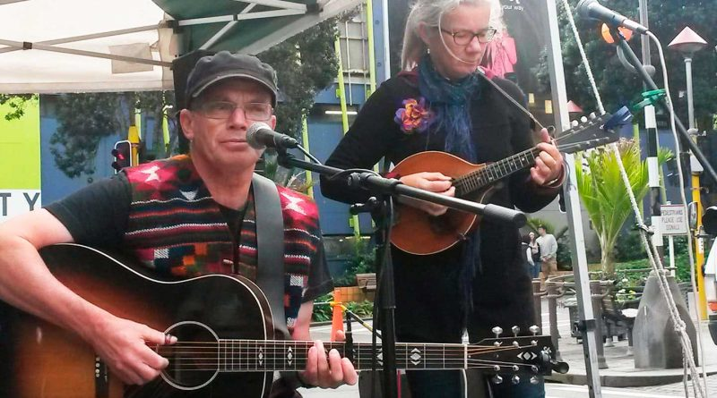 dave murphy and jan muggeridge playing at a market